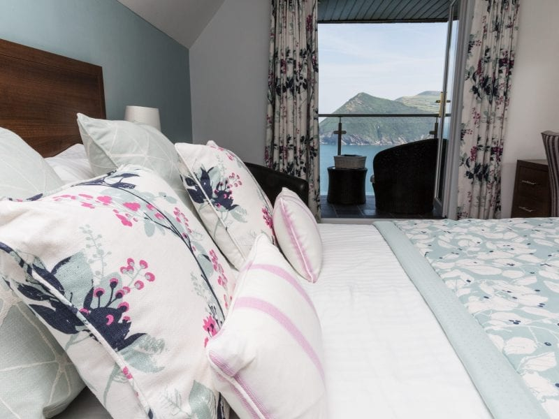 a picture of a bed with floral scatter cushions, throw and curtains with a sea view