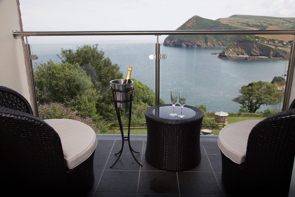 a picture of two black chairs on a balcony overlooking the sea and cliffs with a table, champagne glasses and a champagne bottle in a bucket