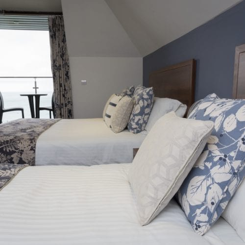 a picture of a bedroom with a large bed, floral throws, curtains, cushions