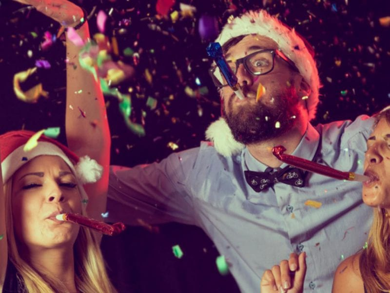 a picture of three people with Christmas hats with party blowers and confetti
