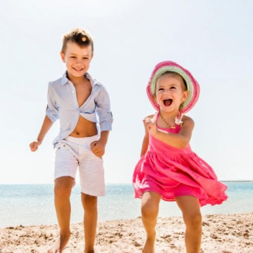 a picture of two children running on the beach with the sea behind them