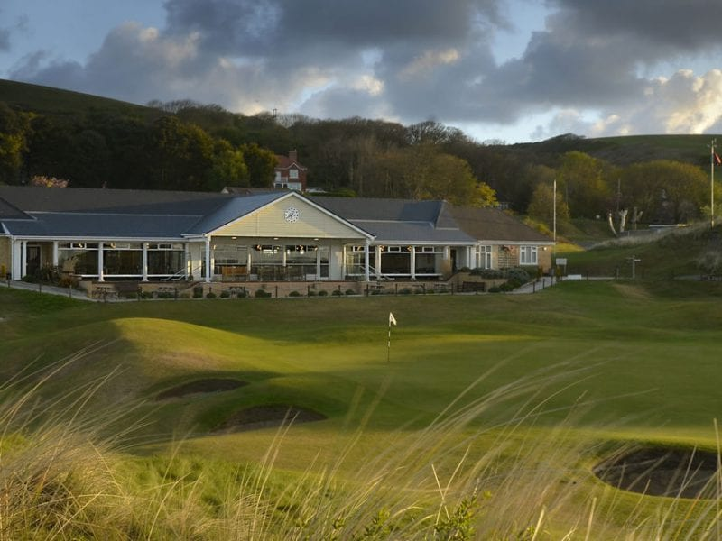 a picture of saunton golf club with lots of green land and a cloudy sky