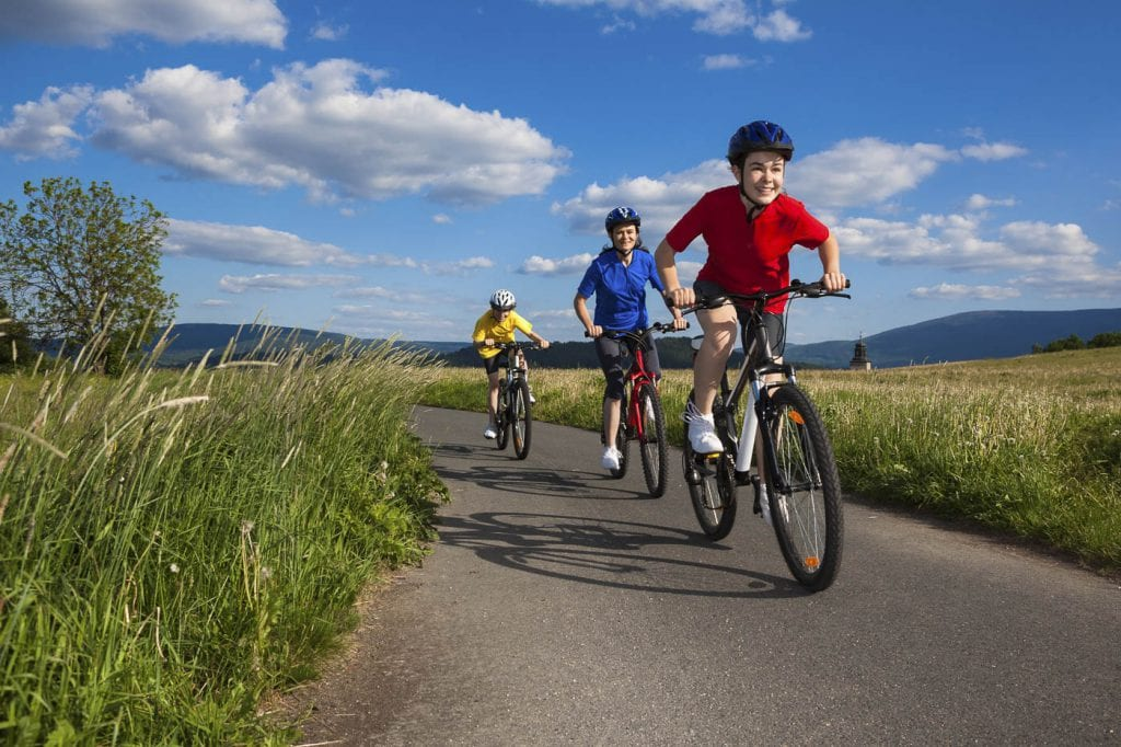 three children on bicycles cycling on a path through the grass with a blue cloudy sky