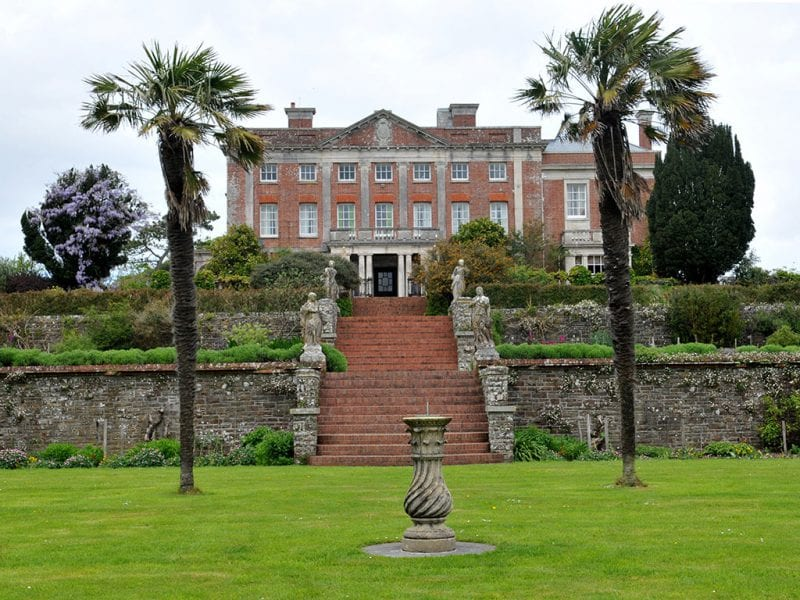 a picture of a large brick building with terracotta window toppers, terracotta steps leading up from the garden with statues and trees