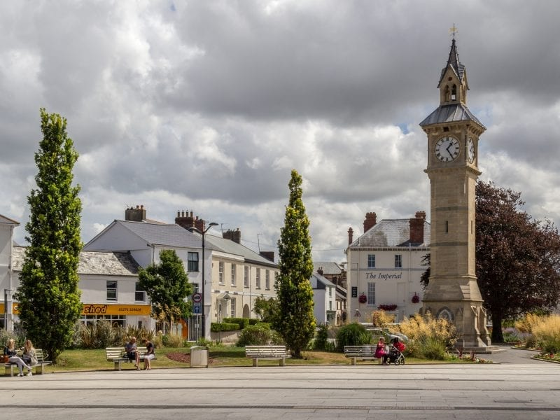 a picture of barnstaple square, with the town clock, trees and people sat on benches