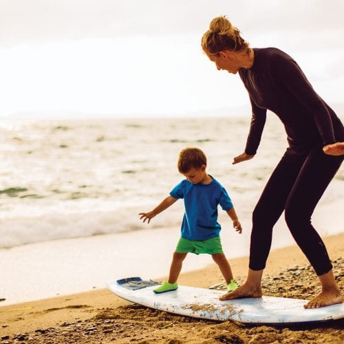 Photo of a little surfer boy and his mother (his instructor) having a surfing class on the beach by the ocean