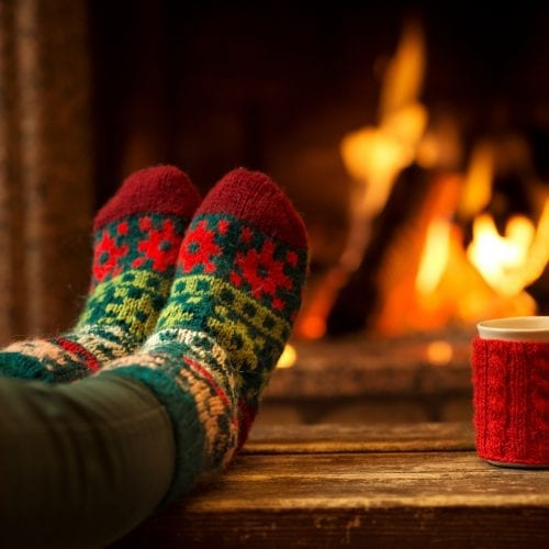 a picture of two feet with festival socks next to a fire, a mug with a knitted jacket