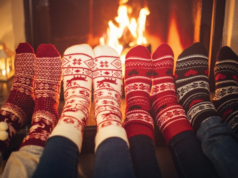 a picture of four pairs of legs with four pairs of socks in front of the fire