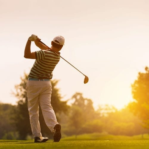 A picture of a man playing golf in the sunset