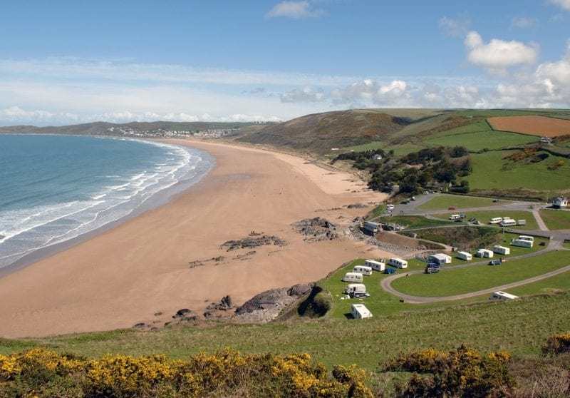 a picture of the coast with a sandy beach, blue sea and green fields