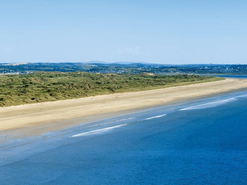 a picture of saunton beach, with a blue sea, sand and a green land area