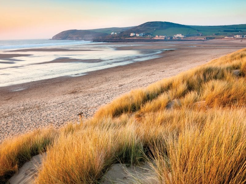 a picture of crowed beach, with golden grass, sand and green fields in the background