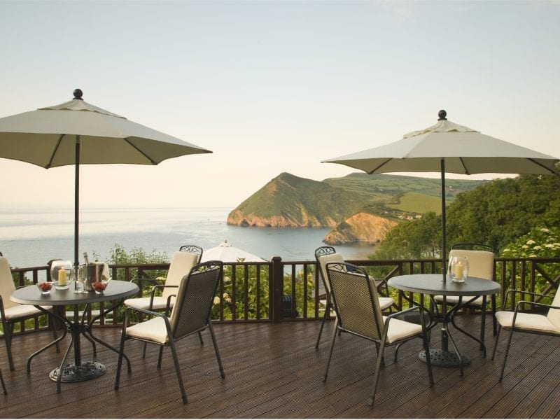 a picture of two tables with parasols outside, over looking a sea view