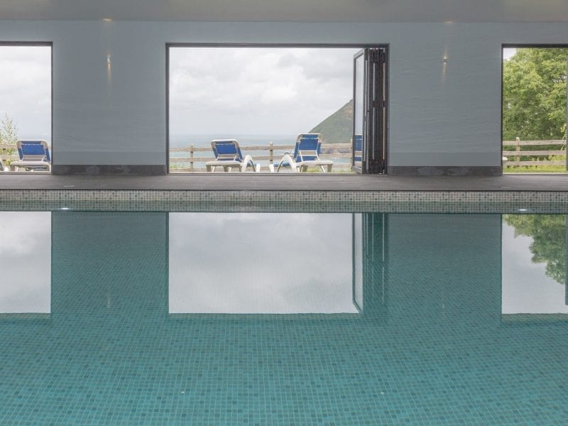 a picture of an indoor pool looking out onto the sea, with deck chairs in the garden
