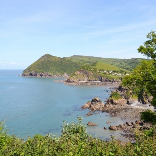 a picture of a sea scape with a blue sky and green land with cliffs edge