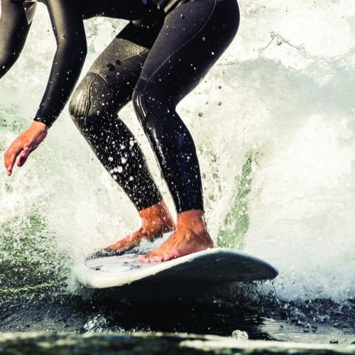a picture of a close up of a man in a wetsuit surfing on the sea
