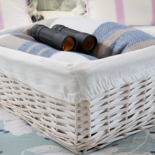 a picture of binoculars and a blanket in a white wicker basket
