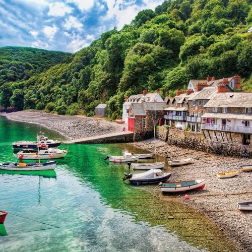 a picture of the bottom of clovelly, with cottages, boats, the sea and trees