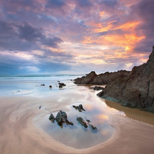 a picture of a beach with clear waters, large cliffs and a sunset
