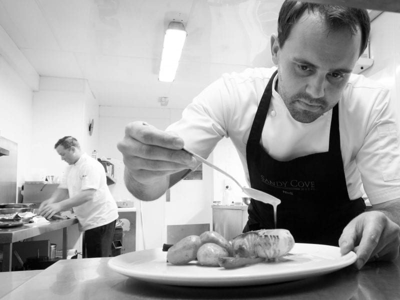 a black and white picture of a chef plating up food in the kitchen