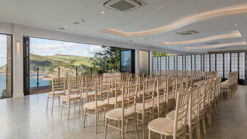 a room filled with rows of beige chairs over looking a sea view
