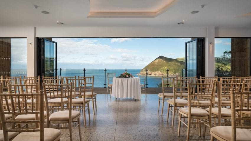 a picture of a room of rowed chairs with a sea view in the background