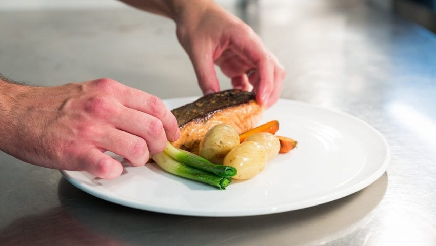 a picture of chef plating up a salmon dish in the kitchen