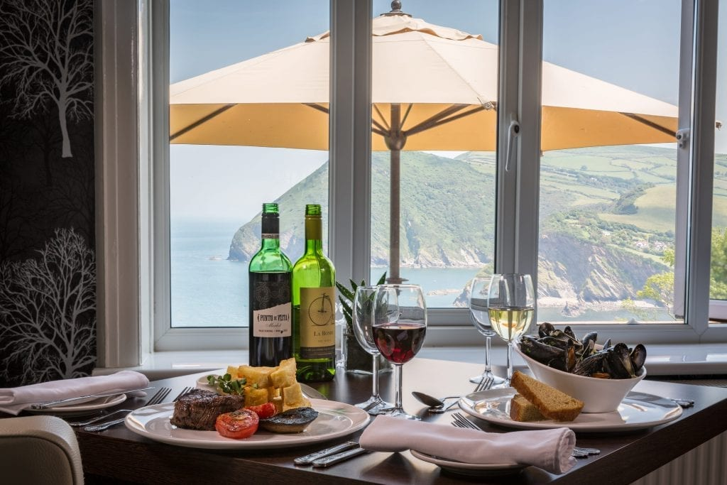 a picture of a table filled with plated food and wine with a sea view