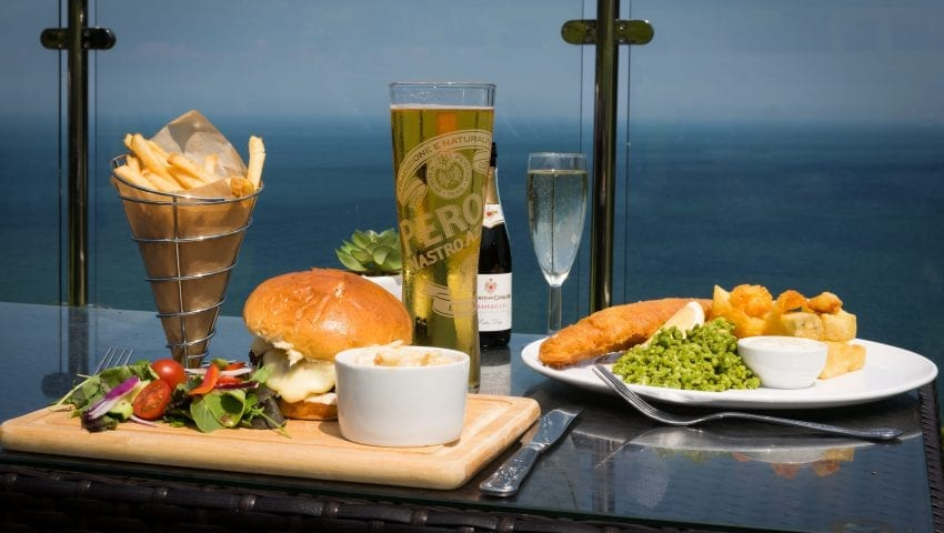 a picture of a plate of fish, chips, peas, a burger, beer a glass of champagne with a sea view