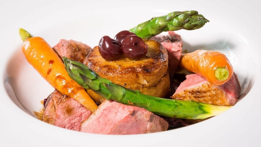 a picture of a bowl of food, carrots, asparagus and meat