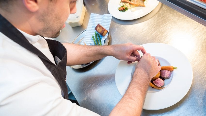 a picture of a chef plating up food in the kitchen