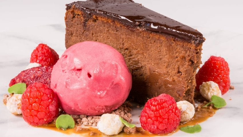 a picture of a chocolate slice garnished with berries and strawberry ice cream