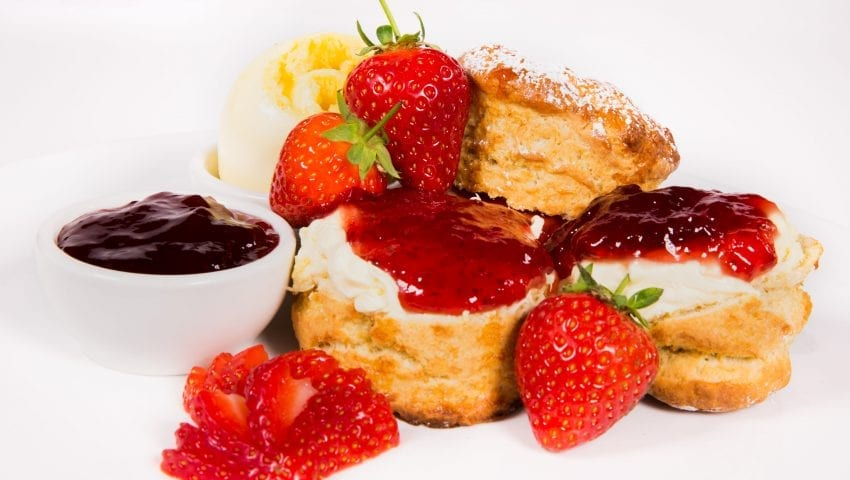 a picture of a plate of scones with cream, jam and strawberries