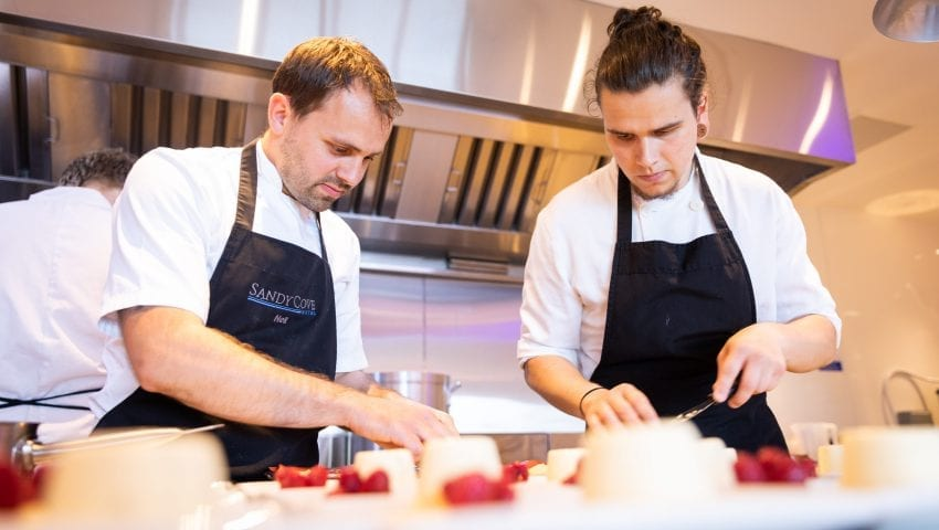 a picture of two chefs in a kitchen plating up desert