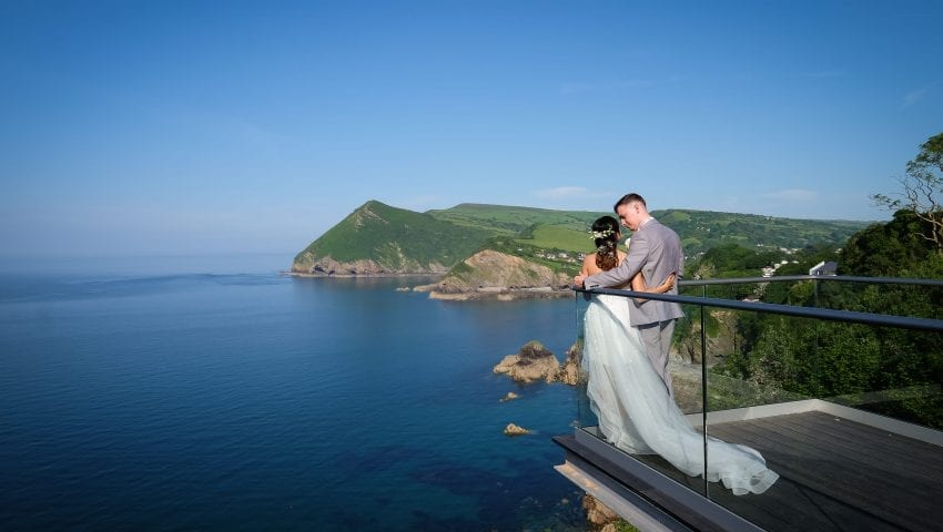 a picture of the bride and groom holding each other at the end of a balcony looking over the sea view
