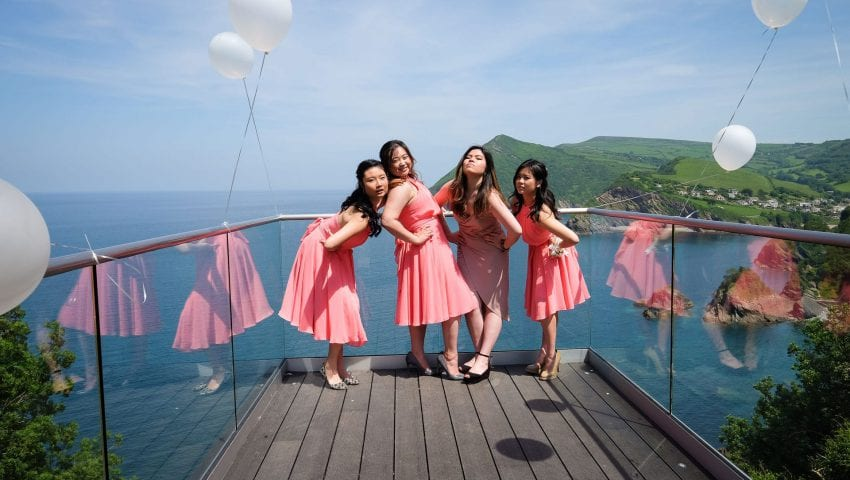 a picture of four women in pink dresses on the end of balcony with white balloons and a sea view