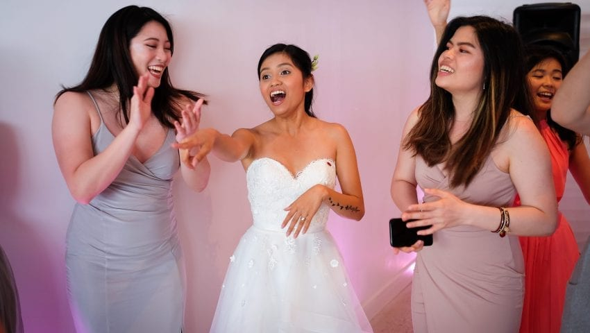 a picture of a bride pointing and laughing with her friends