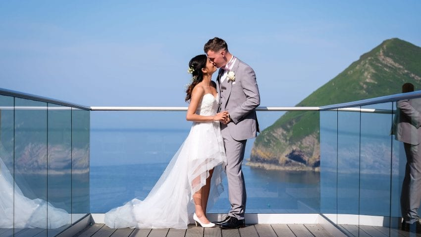 a picture of a couple holding hands smiling at each other at the end of a balcony with a sea view