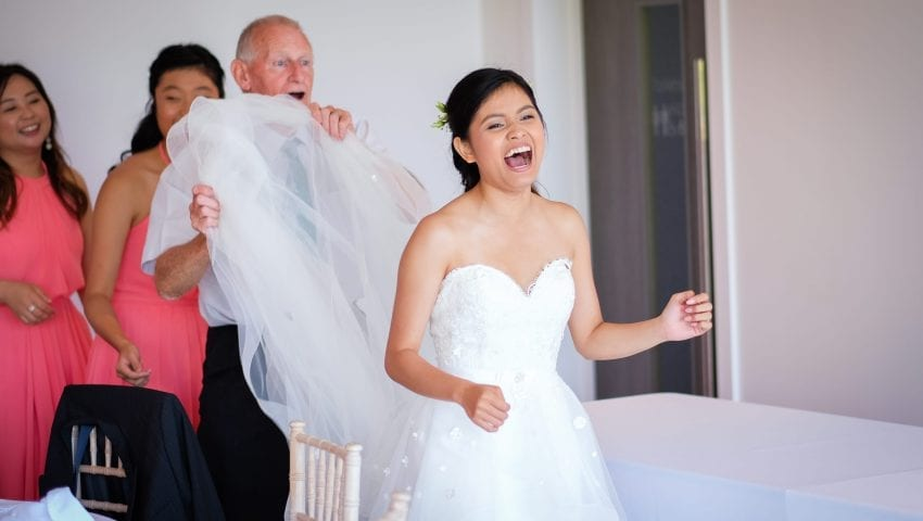 a picture of a bride laughing while a man holds up the dress train