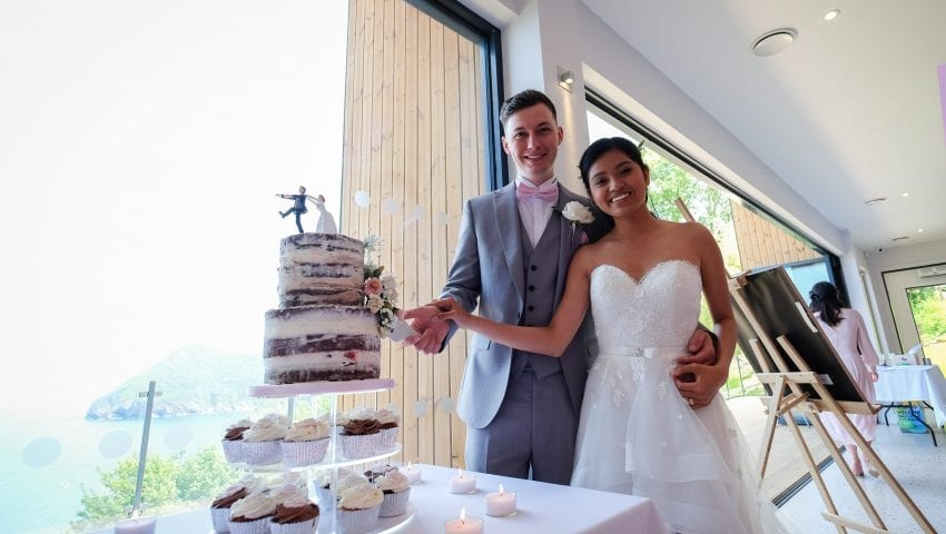 a picture of a couple cutting their wedding cake, smiling at the camera with a sea view in the background