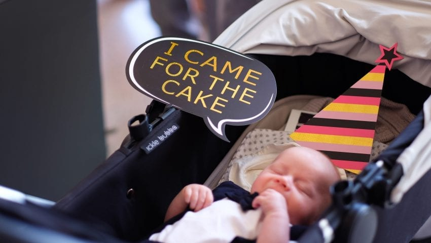 a picture of a baby in a pushchair with a sign