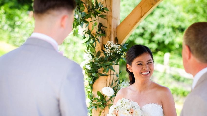 a picture of a bride smiling while holding flowers