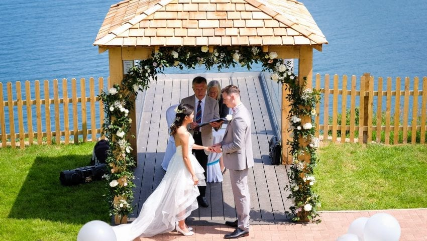 a picture of a couple getting married at the alter under a floral arch with a sea view background