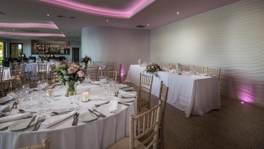a picture of a dining room with laid tables, pink flowers and lights