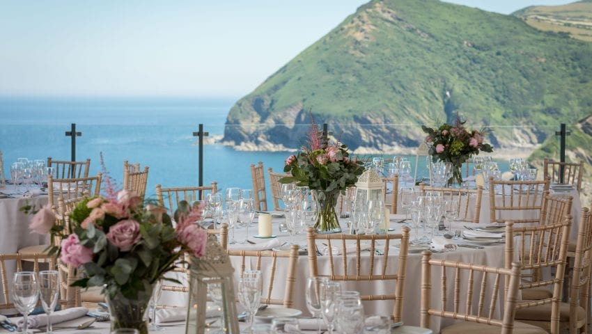a picture of laid tables with pink floral centrepieces outside on a balcony with a sea and cliff view in background