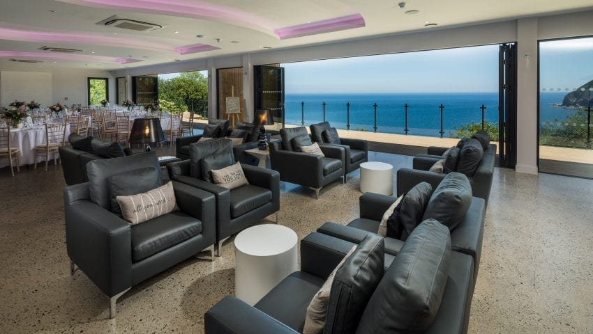 a picture of a lounge room with a view of the dining room and the sea