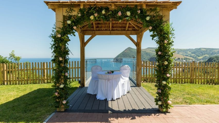 a picture of a floral arch with a white table and chair, a sea view background