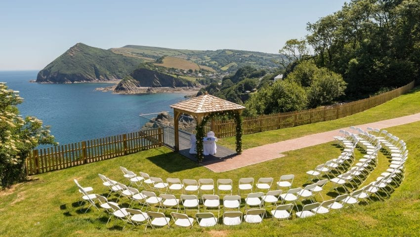 an overview picture of laid out chairs outside, a wedding arch with a sea view and cliffs in the background