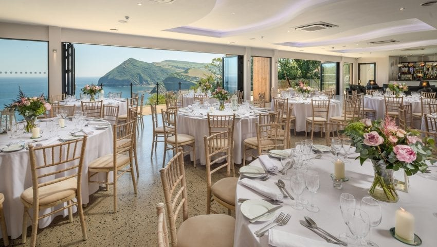 a picture of a dining room with laid tables, pink flower centrepieces and a sea view