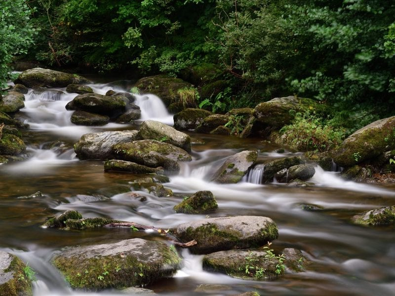 a picture of a flowing river amongst rocks and trees